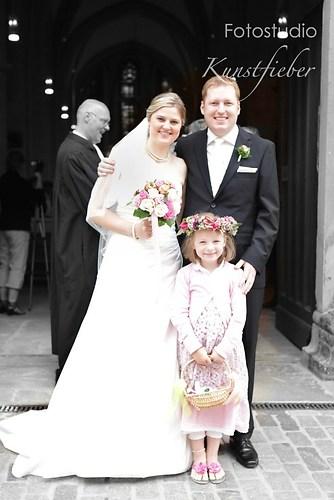 Braut, Bräutigam und Blumenkind vor der Kirche