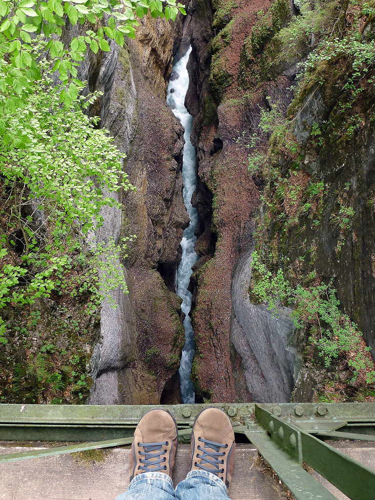 Deep under my feet (Deep under my feet) | High angle view from a iron bridge into a canyon | shoes, deep, high angle view, down, water, bridge, canyon, river, vertigo, mountain, stones, waterfall