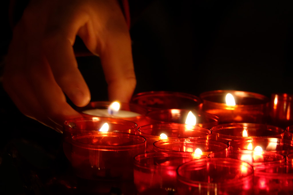 Memory (Memory) | human hand lights candles in a church | glowing, flame, candle, burning, illuminated, tea light, one person, real people, indoors, human hand, lit, close-up, night, human body part, church