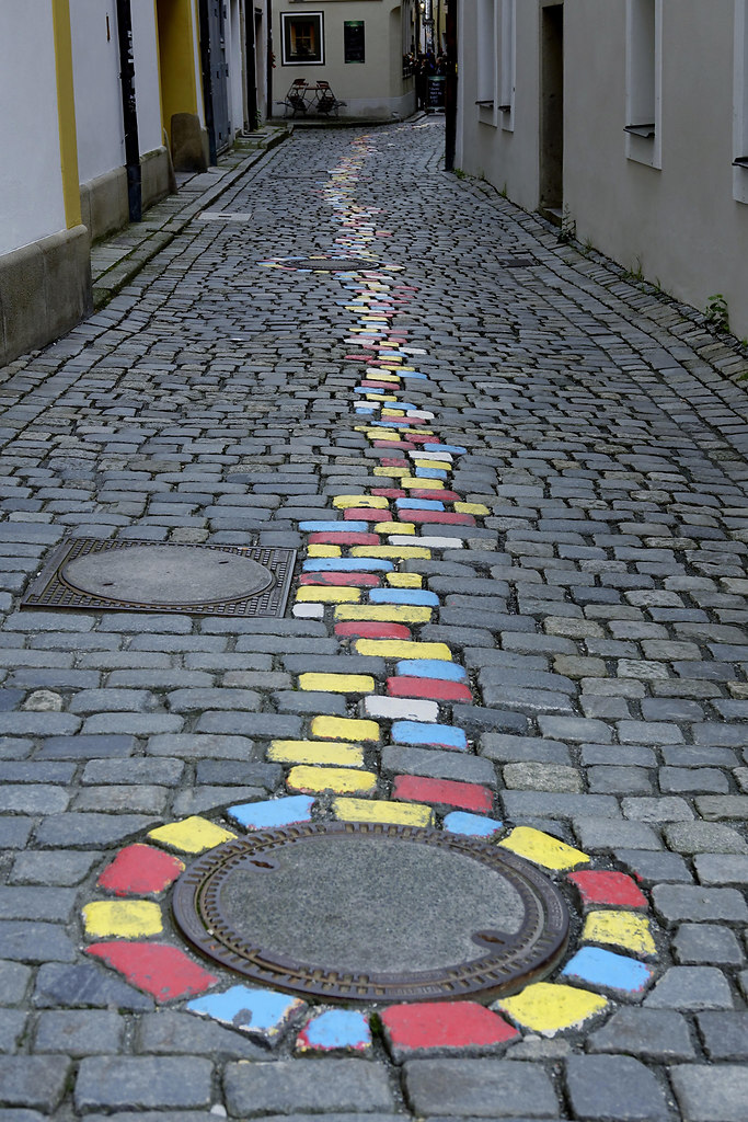 One Way (One Way) | brightly painted cobblestones mark a direction | cobblestones, built structure, outdoors, no people, day, colors, houses, buildings, homes, row of houses, block