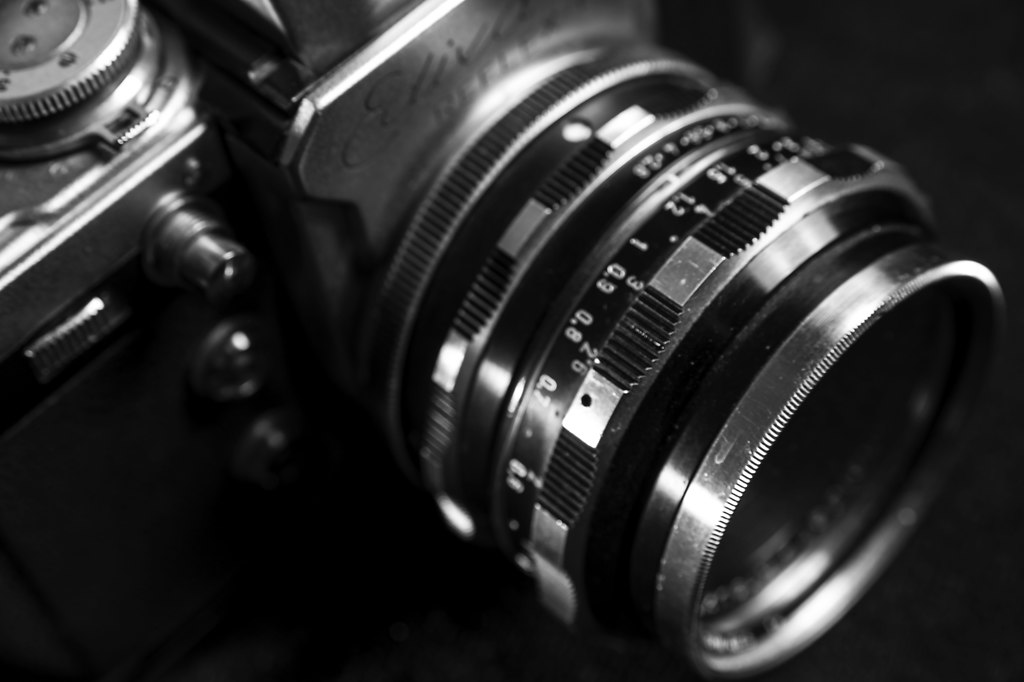 Photo Camera I (Photo Camera I) | Photo Camera I close-up black and white high angle view | camera, lens, close-up, black and white, no people, vintage, high angle view, technology, aperture, equipment, analogue, optics, old, studio, instrument, retro