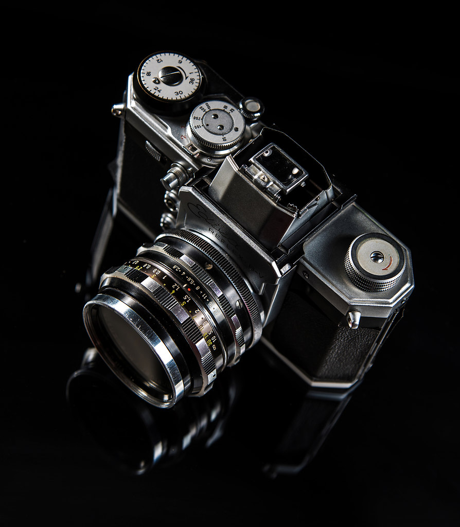 Photo Camera III (Photo Camera III) | Black and silver Photo Camera standing on a glass pane | black background, glass pane, camera, photographic equipment, lens, close-up, shutter, optical instrument, technology, no people, Studio, retro