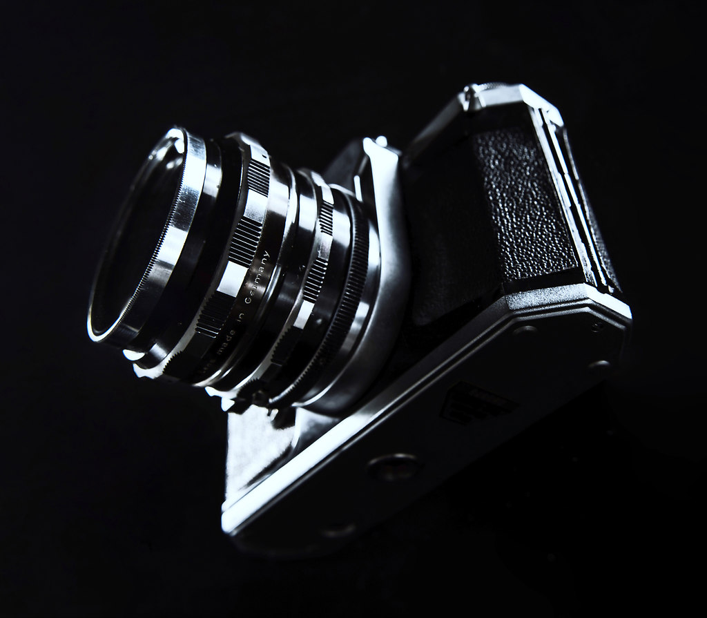 Photo Camera IV (Photo Camera IV) | Black and silver Photo Camera standing on a glass pane | black background, glass pane, camera, photographic equipment, lens, close-up, shutter, optical instrument, technology, no people, Studio, retro