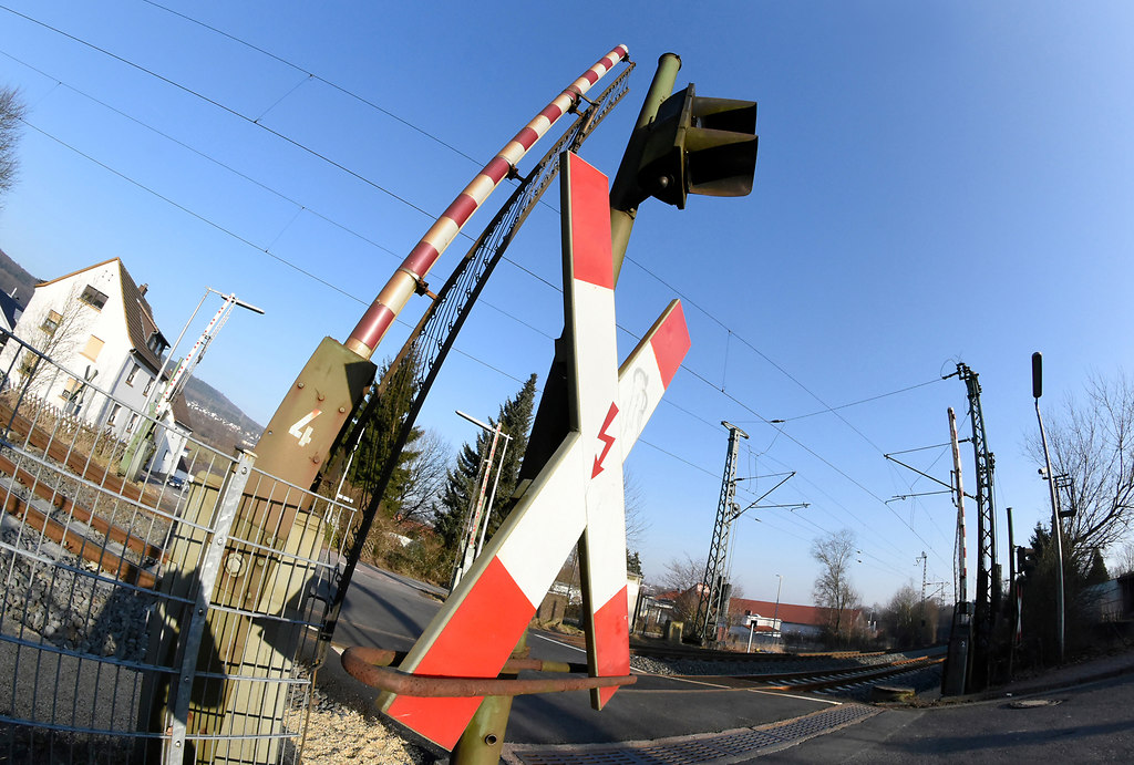 Railroad Crossing (Railroad Crossing) | Railroad crossing low angle view against blue sky open without train | low angle view, railroad, St.Andrew's Cross, outdoors, no people, multi colored, transportation system, travel, industry, business, technology, street, city, urban, architecture, road, traffic, urban, daylight