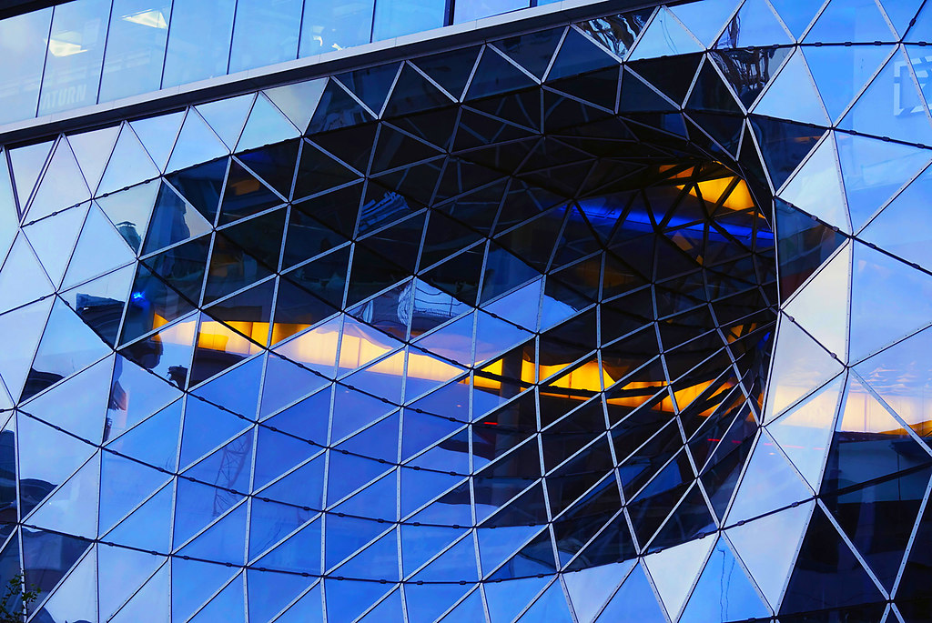 Take a gander at a generous glass facade (Take a gander at a generous glass facade) | Glass facade zoomed in | architecture, glass, generous, facade, lights, yellow, triangles, squares, reflections, windows, low angle view, pattern, built structure, building exterior, illuminated, futuristic, close-up, no people, stock image, images, royalty free photo, stock photos, stock photograph, stock photographs, picture, pictures, graphic, graphics