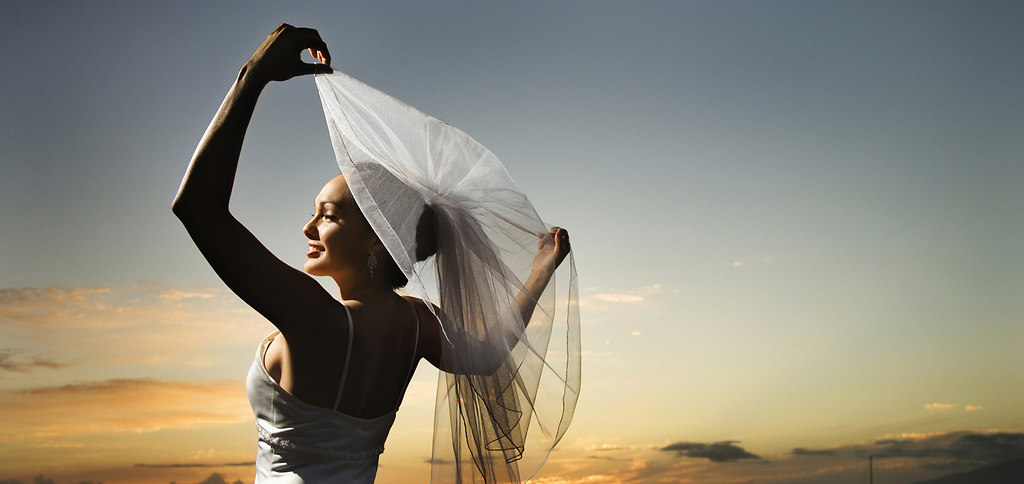 Bride holding out veil on beach. (06) | Young adult female Caucasian bride holding out veil on beach. | colour, color, photograph, image, horizontal, outdoors, marriage, wedding, veil, wedding dress, beach, portrait, bridal, bride, sunset, Caucasian, female, young adult, person, smiling, holding, 20-25 years, half-length, mid-adult woman, one person only, woman, 060426c0014, Multi-racial, copy space