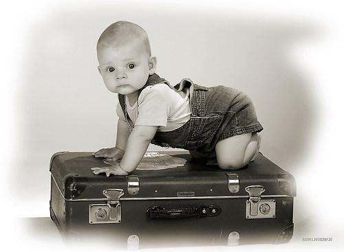 Kind auf Koffer