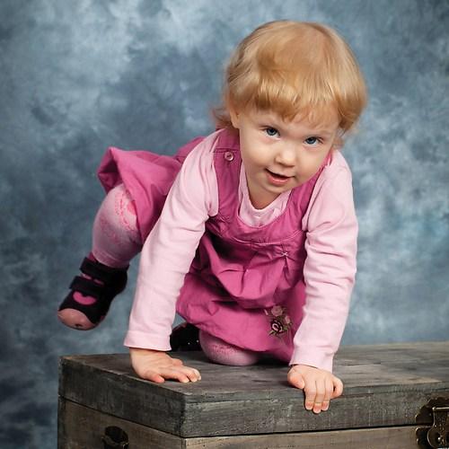 Kleines Mädchen klettert auf Kiste