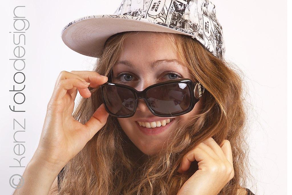 | Junge Frau schaut über ihre grosse Sonnenbrille | Frau, jung, 18, Sonnenbrille, Brille, gross, modisch, Brillenmode, Accessoire, Cap, Baseball-Cap, lachen, lächeln, Blick, blicken, schauen, sehen, Mädchen, Haare, haarig, Locken, lockig, langhaarig, blond, brünett, Jugend, Jugendliche